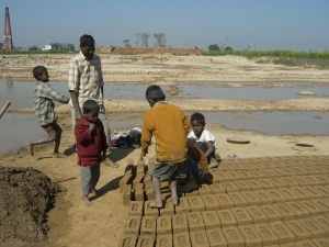 Child bonded labourers turning bricks to dry in Indian kiln